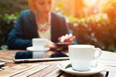 picture of internet-cafe  - Cup of coffee on the foreground with elegant young woman using busy touch screen tablet at the coffee shop wooden table work break of business people flare sun light - JPG