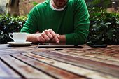 stock photo of coffee crop  - Cropped image young man sitting at the table with cup of coffee digital tablet and smart phone man