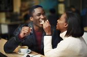 foto of dark-skin  - Beautiful dark skinned couple in love having a great time together man and woman enjoying each other young woman feeding man with dessert cake at their dating - JPG