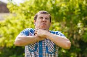 picture of choke  - Man on the street choking himself hands on a green background leaves summer - JPG