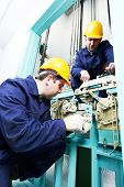 picture of elevator  - two male technician machinist worker at work adjusting elevator mechanism of lift with spanner - JPG