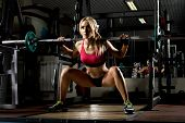 image of execution  - beautiful girl bodybuilder execute exercise with weight in dark gym - JPG