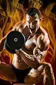picture of execution  - very power athletic guy execute hard exercise with dumbbells on flame background - JPG