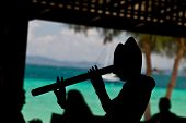 picture of flute  - silhouette of statue playing flute at the Beach in thailand - JPG