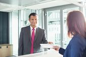 foto of receptionist  - Businessman receiving document from receptionist in office - JPG