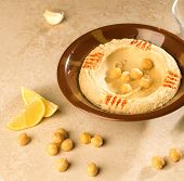 pic of chickpea  - Bowl of Hummus with raw chickpeas and lime wages - JPG
