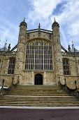 stock photo of chapels  - Low Angle View of Stairs and Facade of St Georges Chapel at Windsor Castle in England Framed by Blue Sky - JPG