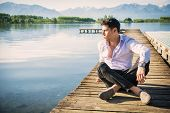 image of pier a lake  - Handsome young man on a lake in a sunny - JPG