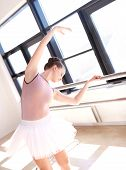 picture of ballet barre  - Young Ballerina Wearing Pink Tutu Stretching at Barre in Sunny Dance Studio - JPG