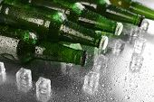 image of wet  - Glass bottles of beer with ice cubes on wet table background - JPG