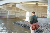 stock photo of street-rod  - Man casting with light rod on the river near the bridge - JPG