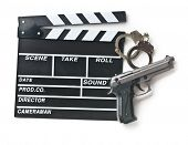 picture of top-gun  - movie clapper and gun with handcuffs on white background - JPG
