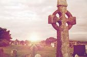 ancient monument and burial concept - old grave cross, headstones and ruins on celtic cemetery grave poster