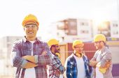 business, building, construction and people concept - group of smiling builders in hardhats outdoors poster