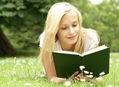 stock photo of reading book  - Young beautiful girl reading a book outdoor - JPG