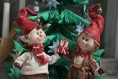 Christmas Elfs Boy And Girl Giving A Present Under Christmas Tree  (horizontal)