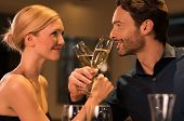Young happy couple toasting with glass of champagne on romantic date at luxury restaurant. Portrait  poster