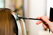 At the hairdresser �¢�?�? woman gets new hair colour; close-up on strand of hair
