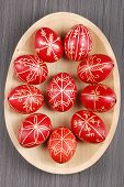 picture of easter-eggs  - Traditional red coloured hand painted easter eggs on a woodplate - JPG