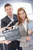 Attractive businesspeople with clapper board, during shooting a film, smiling.?