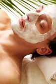 Young man having pore cleaning procedure in parlor