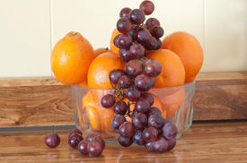 picture of tangelo  - Fruit still life with bowl of tangelos with red grapes hanging and falling from bowl - JPG