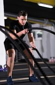 young fit athlete man working out in functional training gym doing  battle ropes exercise as part of poster