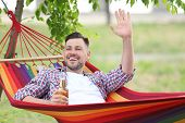 Handsome Young Man With Bottle Of Beer Resting In Hammock Outdoors poster