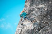 Rock Climber On A Rock. Woman Climbs The Rock On The Background Of A Beautiful Sky With Clouds. Acti poster