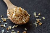 Natural Brown Sugar Or No Bleach Sugar On Wood Spoon. Organic Brown Sugar On Black Granite Table In  poster
