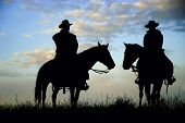 foto of wild west  - Cowboys on a Montana ridge at dawn back lit by the rising sun - JPG