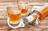 Bottle And Glasses With Alcohol Drink And Handcuffs On Wooden Table. Alcohol Dependence. poster