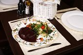Elegant Restaurant Plate With A Big Steak And Gravy Garnished With Steamed Vegetables.