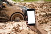 Man Hand Holding Smartphone With White Screen Display Use For Mock Up. Car Tire Stuck In The Mud Bac poster