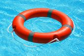 Red Lifebuoy Pool Ring Float On Blue Water. Life Ring Floating On Top Of Sunny Blue Water. Life Ring poster