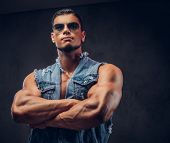 Sexy Naked Fashionable Confident Male With A Muscular Body In A Denim Vest And Sunglasses Poses With poster