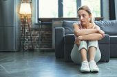 Mood Swing. Depressed Mature Woman Sitting On Floor And Hugging Knees poster