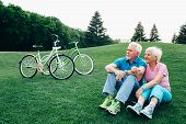 Happy Senior Couple Sits On The Grass, Enjoying The Rest After Riding Bicycles. Bicycles Stand Next  poster