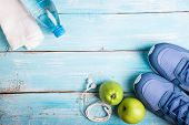 Flat Lay Sport Shoes, Bottle Of Water, Apples, Towel And Earphones On Blue Background. Sport Equipme poster