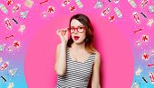 Portrait Of Beautiful Surprised Young Woman In Glasses On The Wonderful Pink Studio Background And W poster