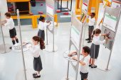 School kids doing science tests at a science centre poster