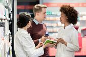 Portrait of a female experienced pharmacist reading the indications from the package of a new pharma poster