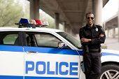 Handsome African American Police Officer With Crossed Arms Leaning Back On Car And Looking At Camera poster