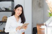 Beautiful Portrait Young Asian Woman Using Tablet Computer In The Coffee Shop, Businesswoman Sitting poster