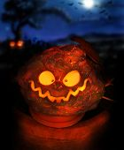 Spooky Halloween image of a glowing jackolantern with eerie night sky in background including moon a