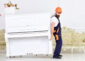 Loader Moves Piano Instrument. Heavy Loads Concept. Man With Beard Worker In Helmet And Overalls Lif poster