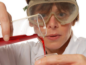stock photo of mad scientist  - careful young lady scientist in white coat pouring liquid isolated on white - JPG
