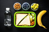 Lunch Box With Sandwich, Vegetables, Banana, Water, Nuts And Berries. Healthy Lunch Food To Go. Top  poster
