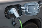 Close-up Shot Of Fully Electric Car Power Cable Socket With Charging Cable Attached poster