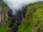 Tourist Woman Standing On Cliff At Voringsfossen Waterfall. Mabodalen Canyon Norway. National Touris poster